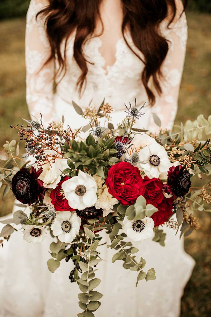 bride holding free form burgundy and white bridal bouquet