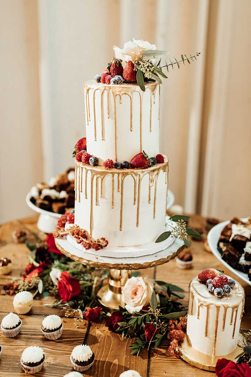 gold dripped white wedding cake with mixed berries on it