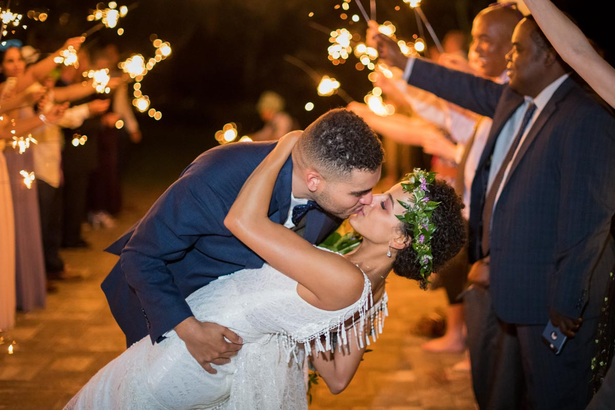 couple kissing under sparkler grand exit