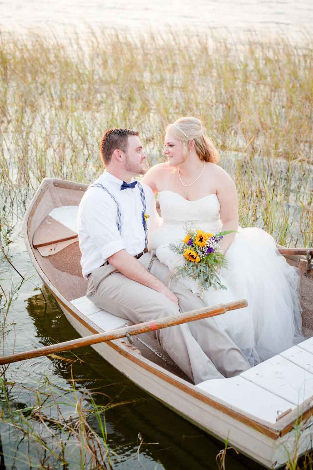 bride and groom in canoe for wedding portraits