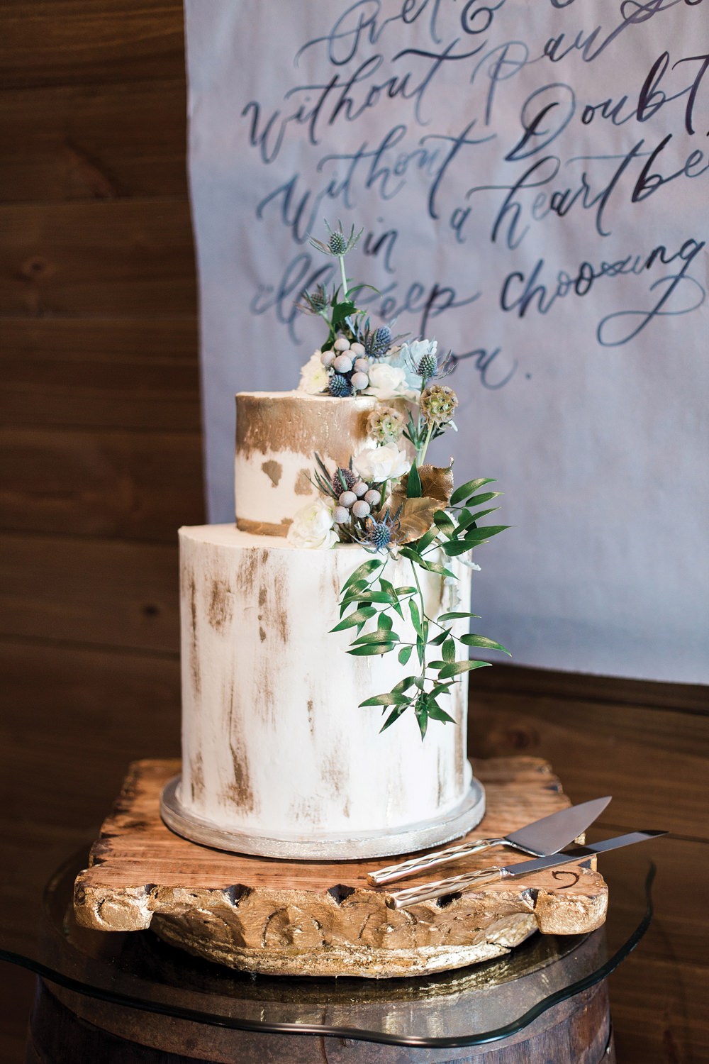 Two tiered white and gold wedding cake with blue thistle on top.