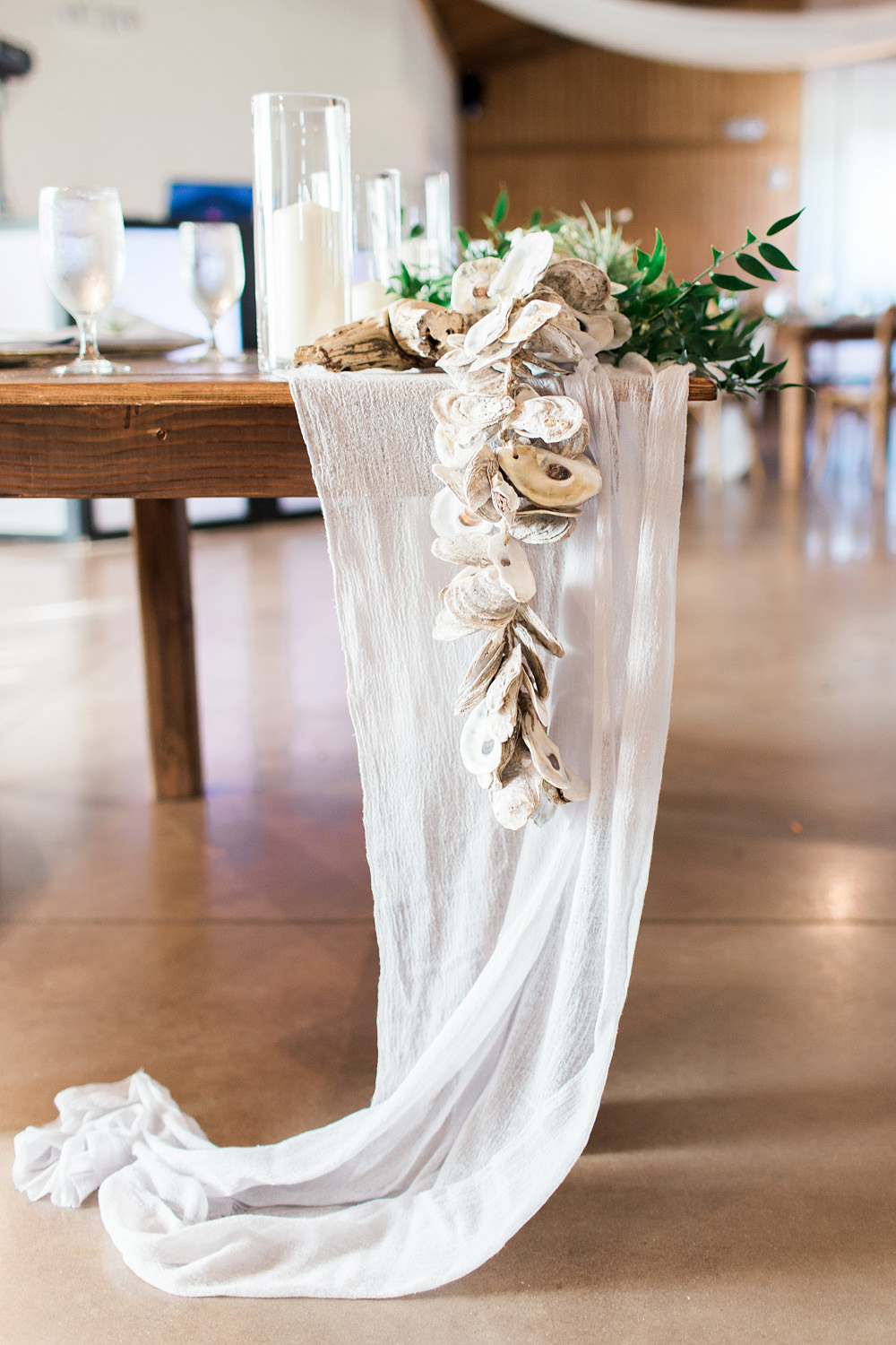 White cheesecloth runner using strands of shells as decor.