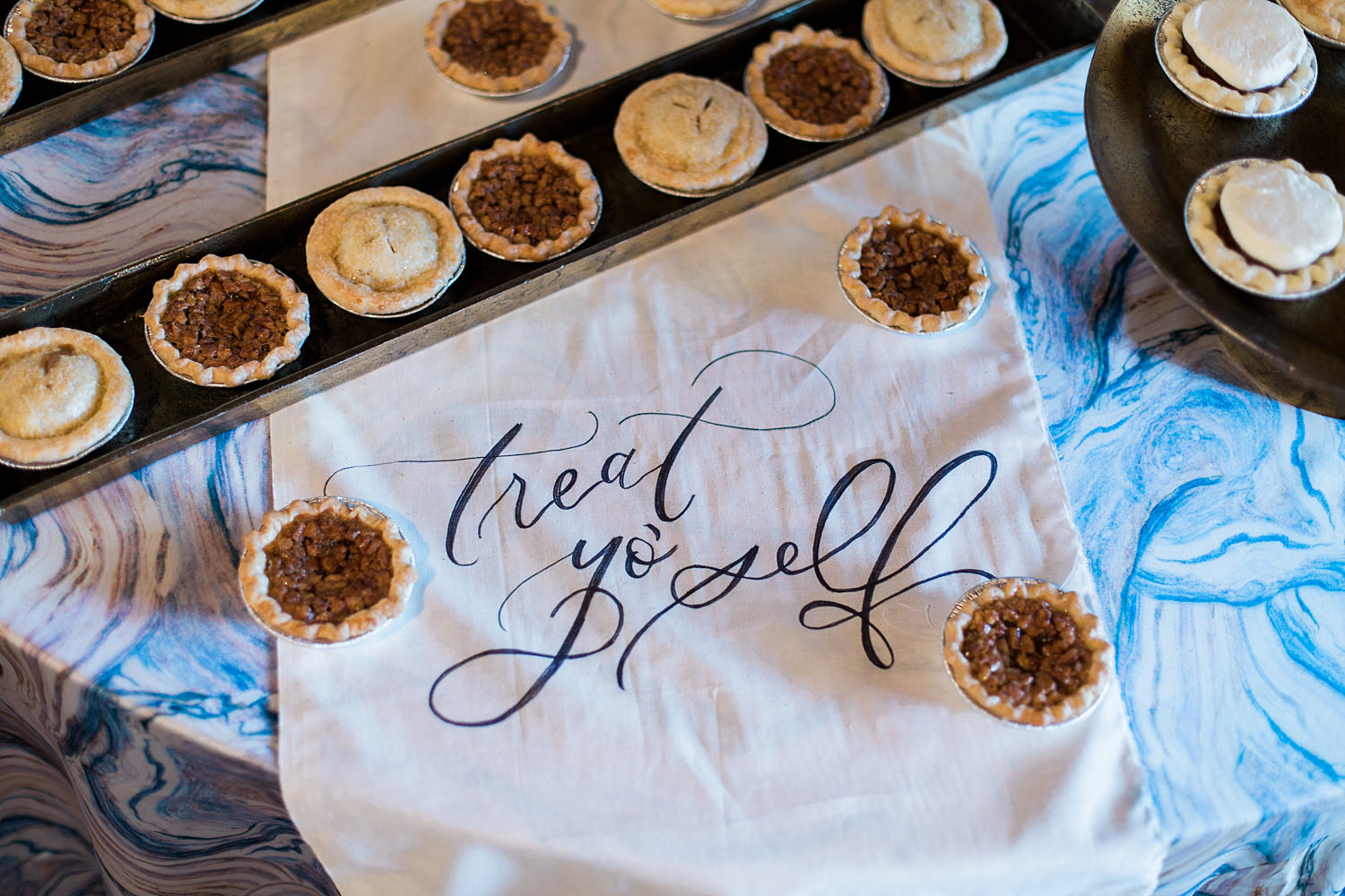 Mini pies for a wedding reception on top of a handwritten table runner.