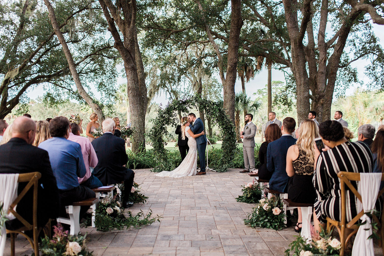 First kiss at an outdoor wedding with an infinity arch in the background.