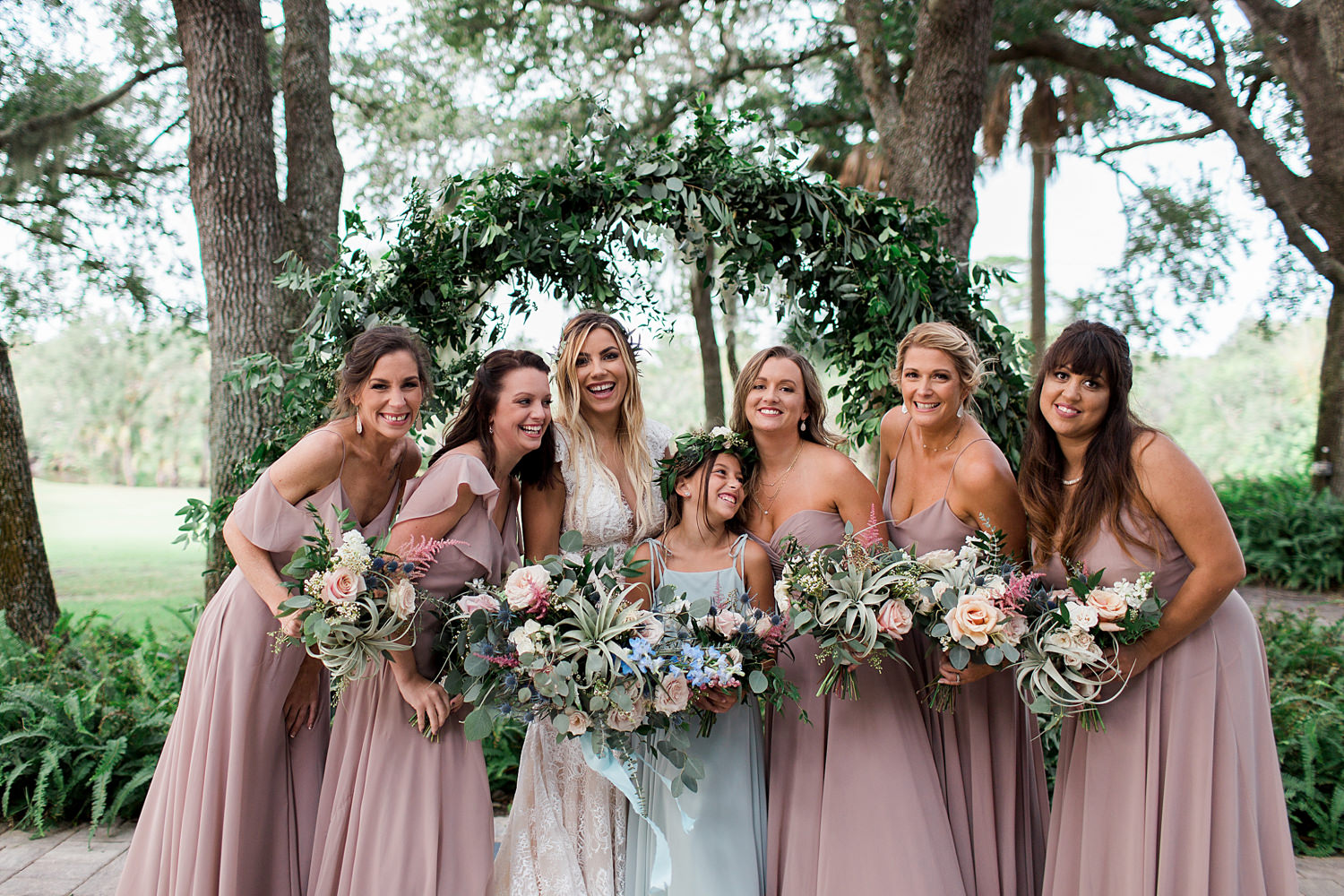 Bride and bridesmaids holding bouquets in front of a greenery infinity arch.
