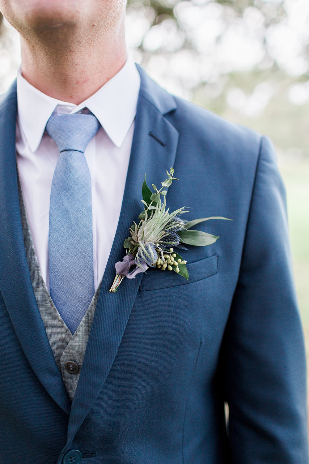 Groom in a blue suit wearing a blue thistle boutonniere.
