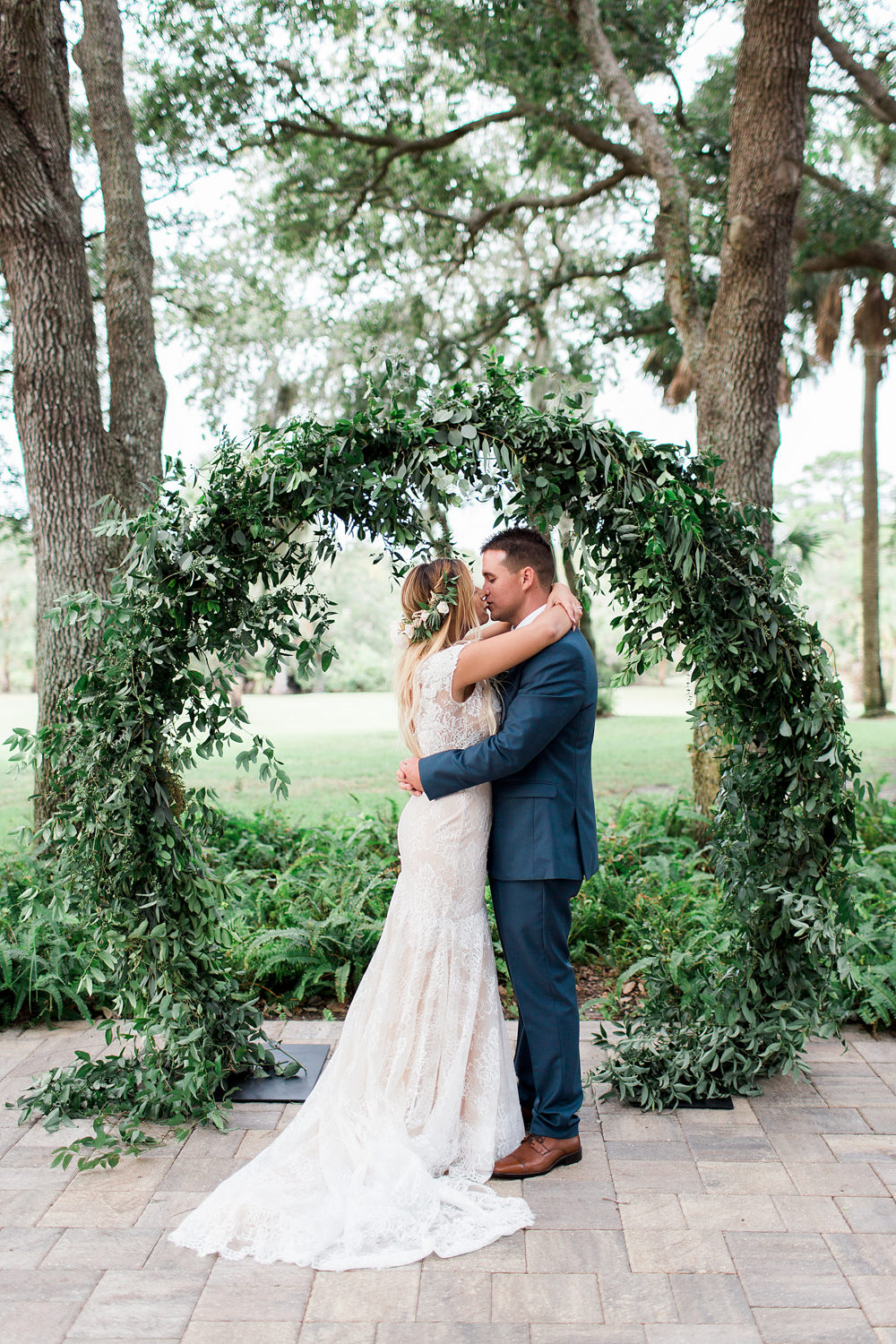Bride and groom kissing in front of a greenery filled infinity arch.