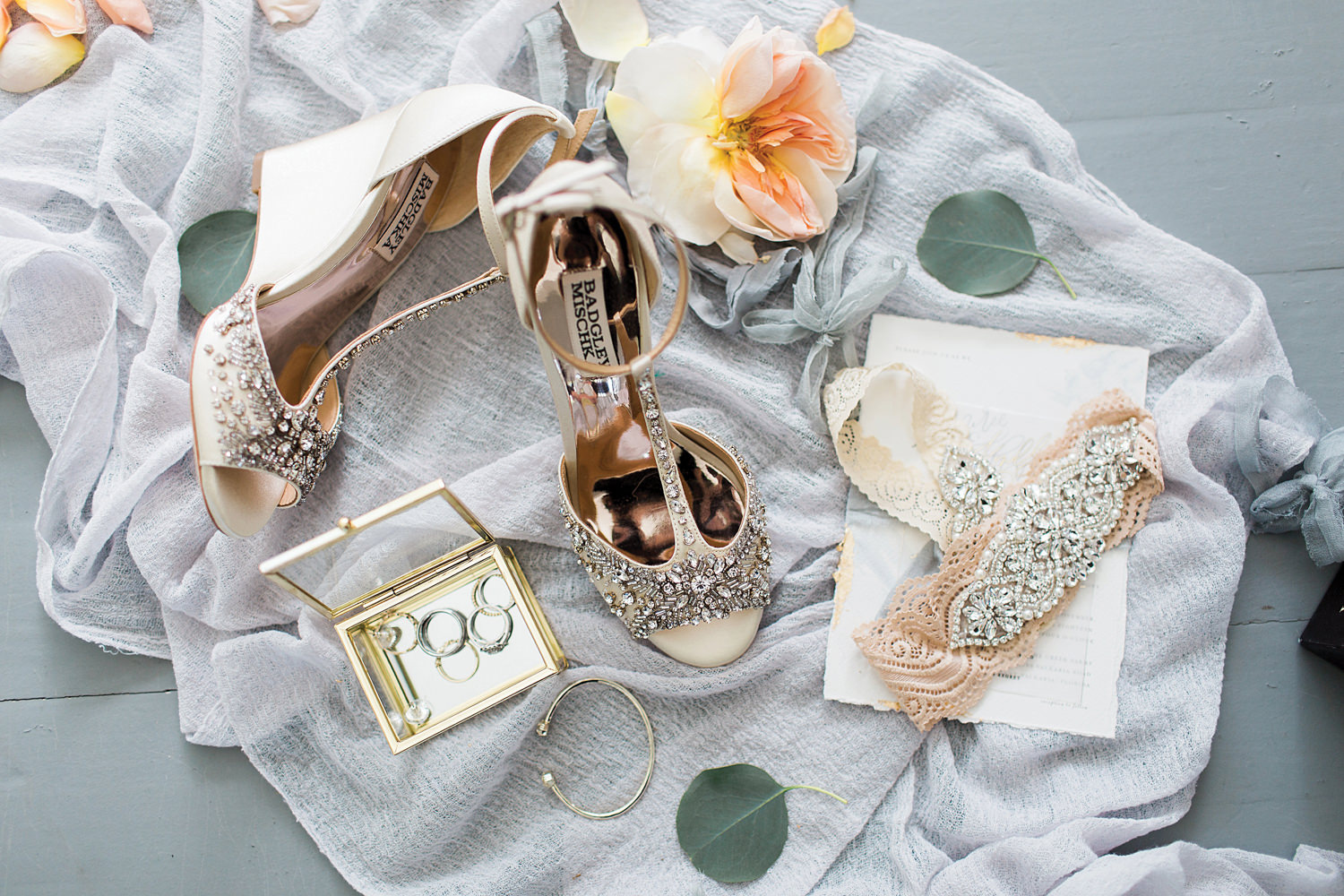 Flatlay of bridal details including garter, jewelry, and badgley mishka wedding shoes.
