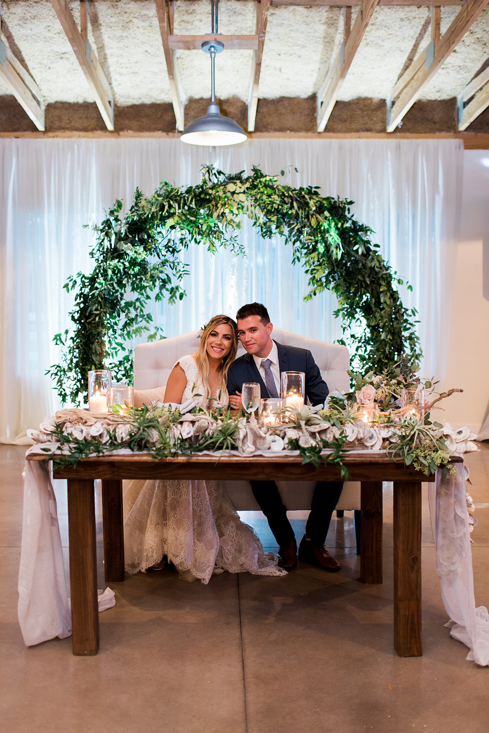 Sweetheart table using an infinity arch and white draping as the backdrop.