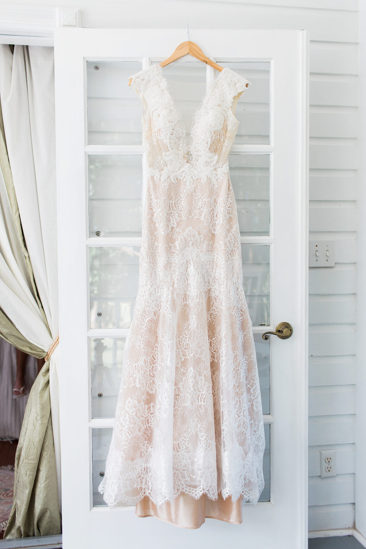 Blush wedding dress hanging on a white door.