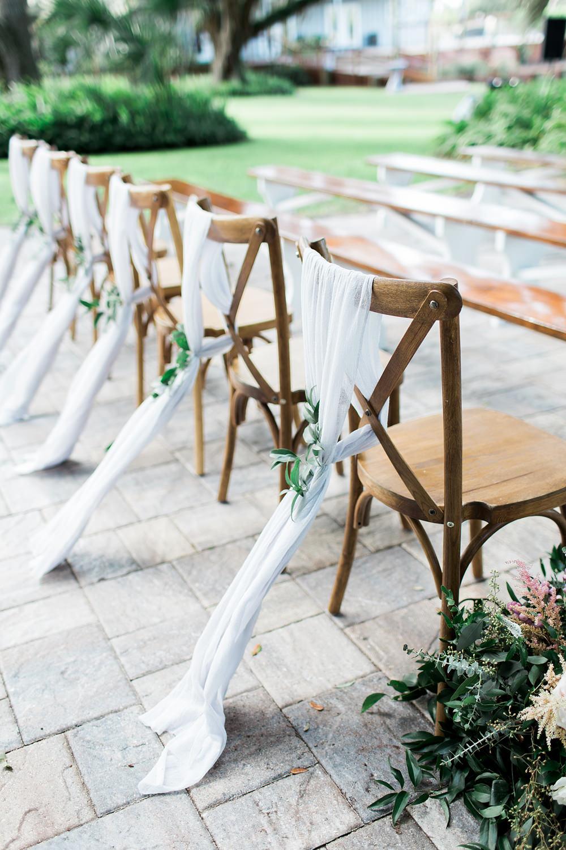 White chiffon hanging off the back of chiavari chairs.