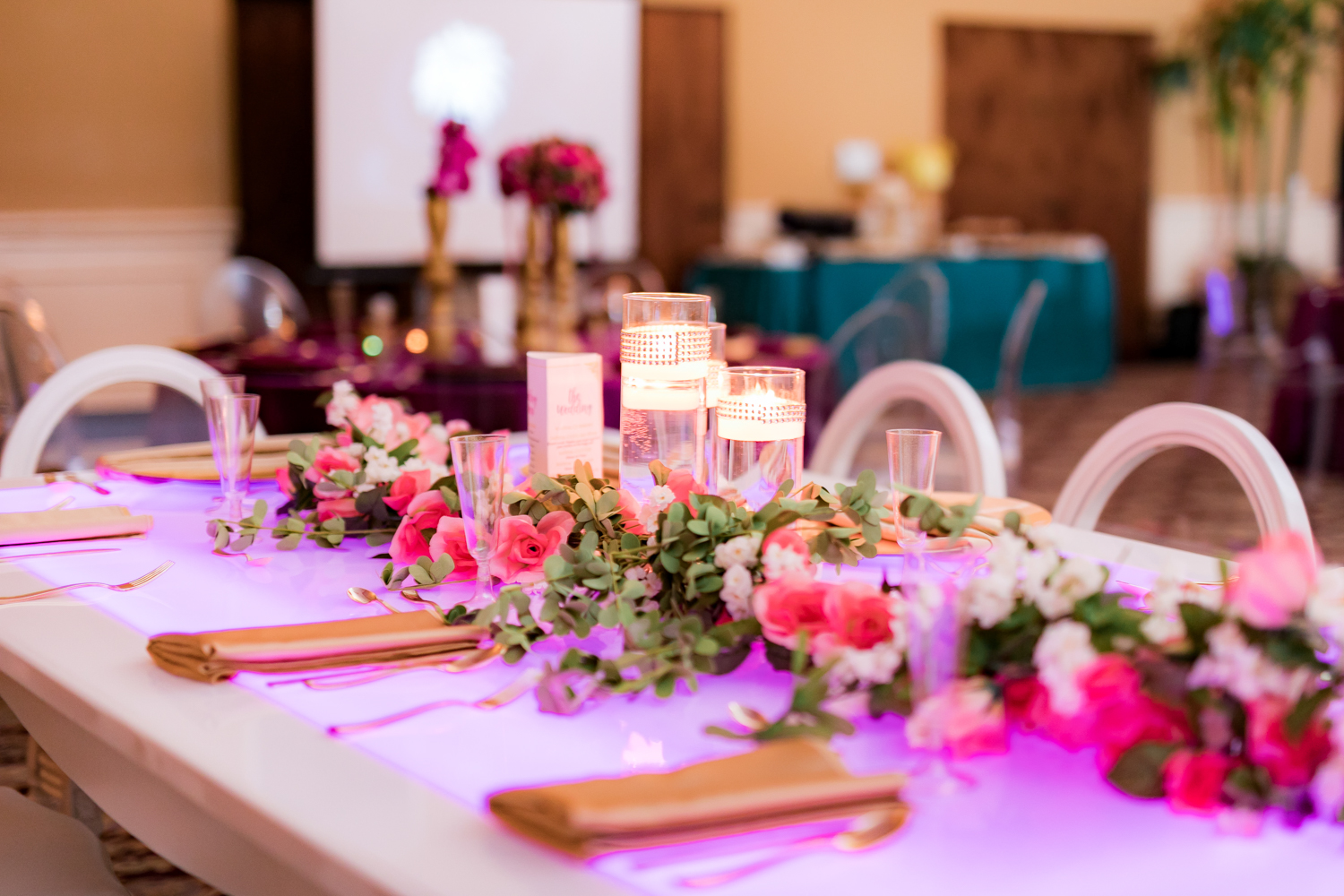 Pink and purple wedding reception table lit with led lighting.