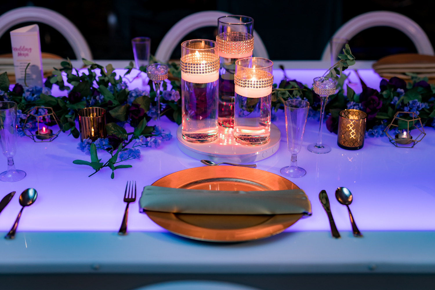Purple wedding reception table lit with led lighting and accented with gold decor.