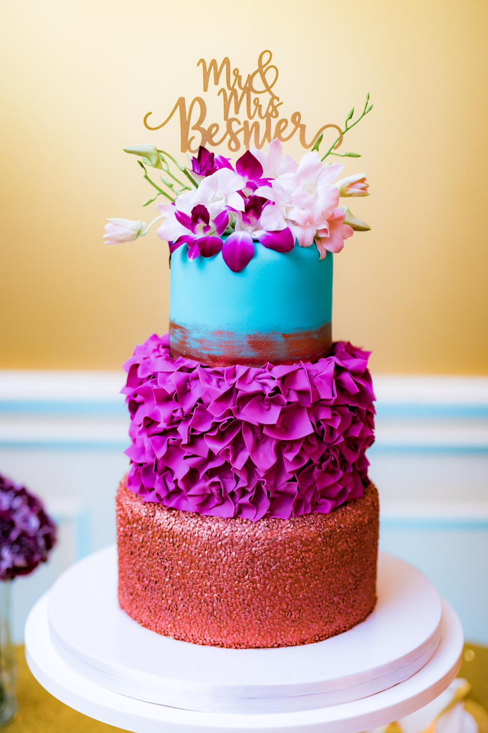 Colorful 3 tiered wedding cake with red, purple, and blue, topped with fresh flowers.