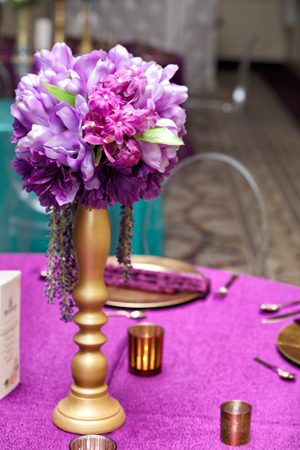 Vibrant purple wedding centerpiece on top of a purple linen, accented with gold decor.