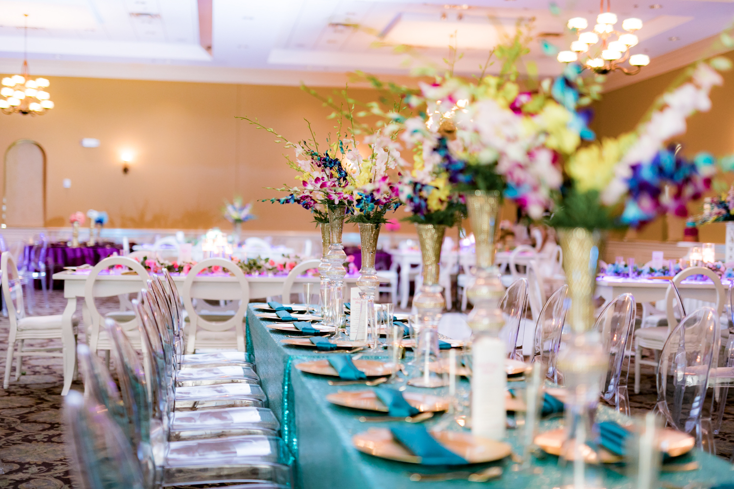 Vibrant blue table linens topped with colorful flower arrangements.