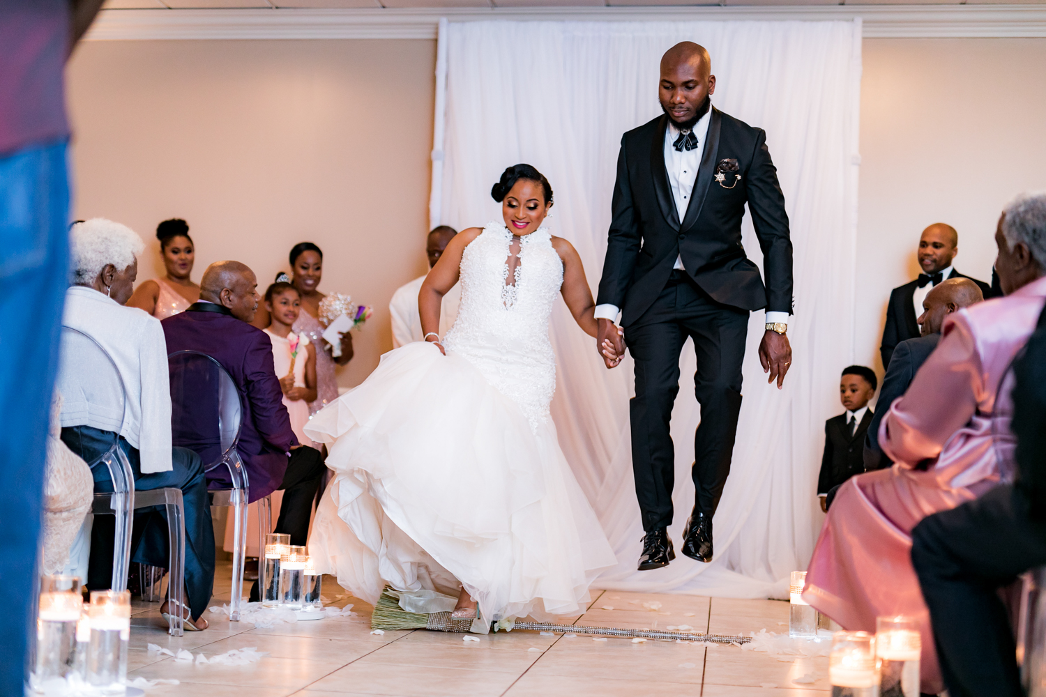 Bride and groom jumping the broom.