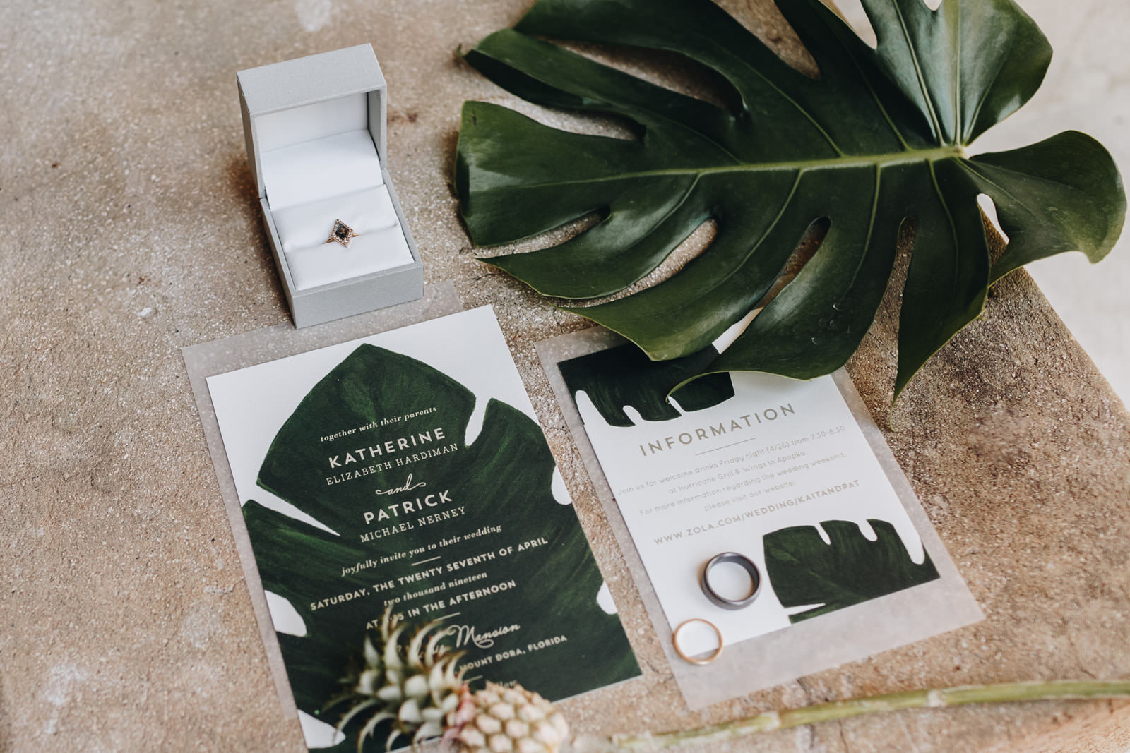 Tropical wedding invitations with wedding rings on top of them.