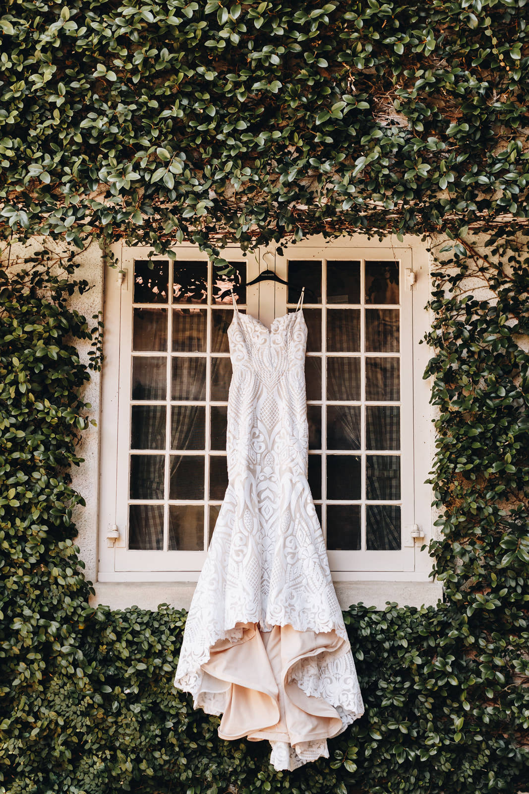 Wedding dress hanging on a window on a greenery wall at Sydonie Mansion.