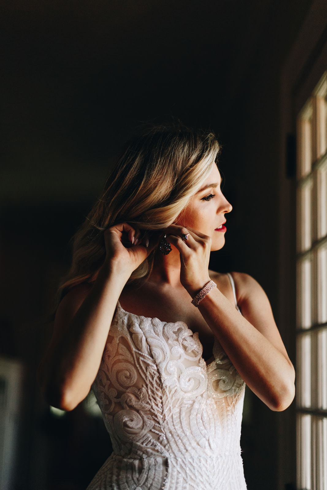 Bride putting her earring on, getting ready for her wedding.