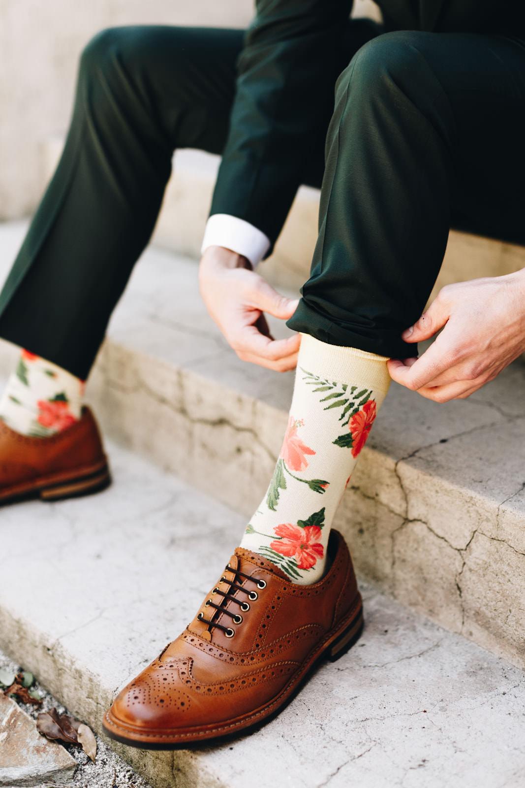 Groom getting ready, putting on tropical flower socks.