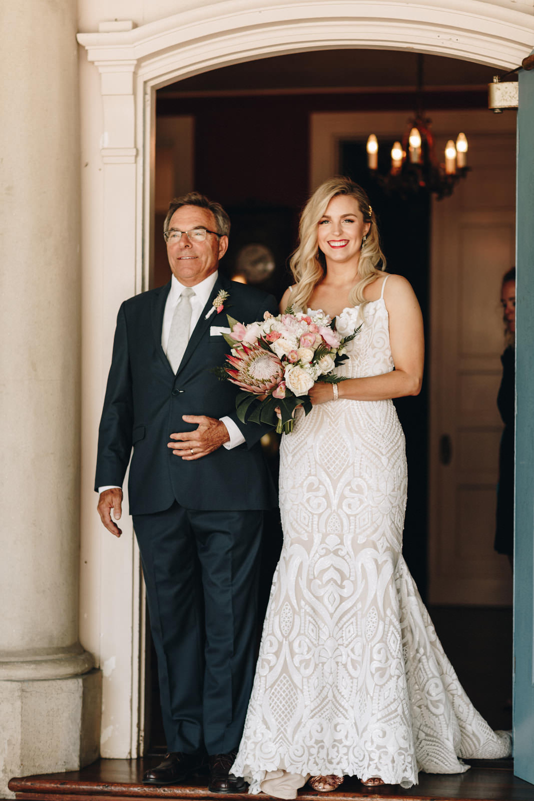 Bride walking out of her mansion wedding venue with her father. She is wearing a spaghetti strap vintage dress and carrying a bridal bouquet with a large king protea.