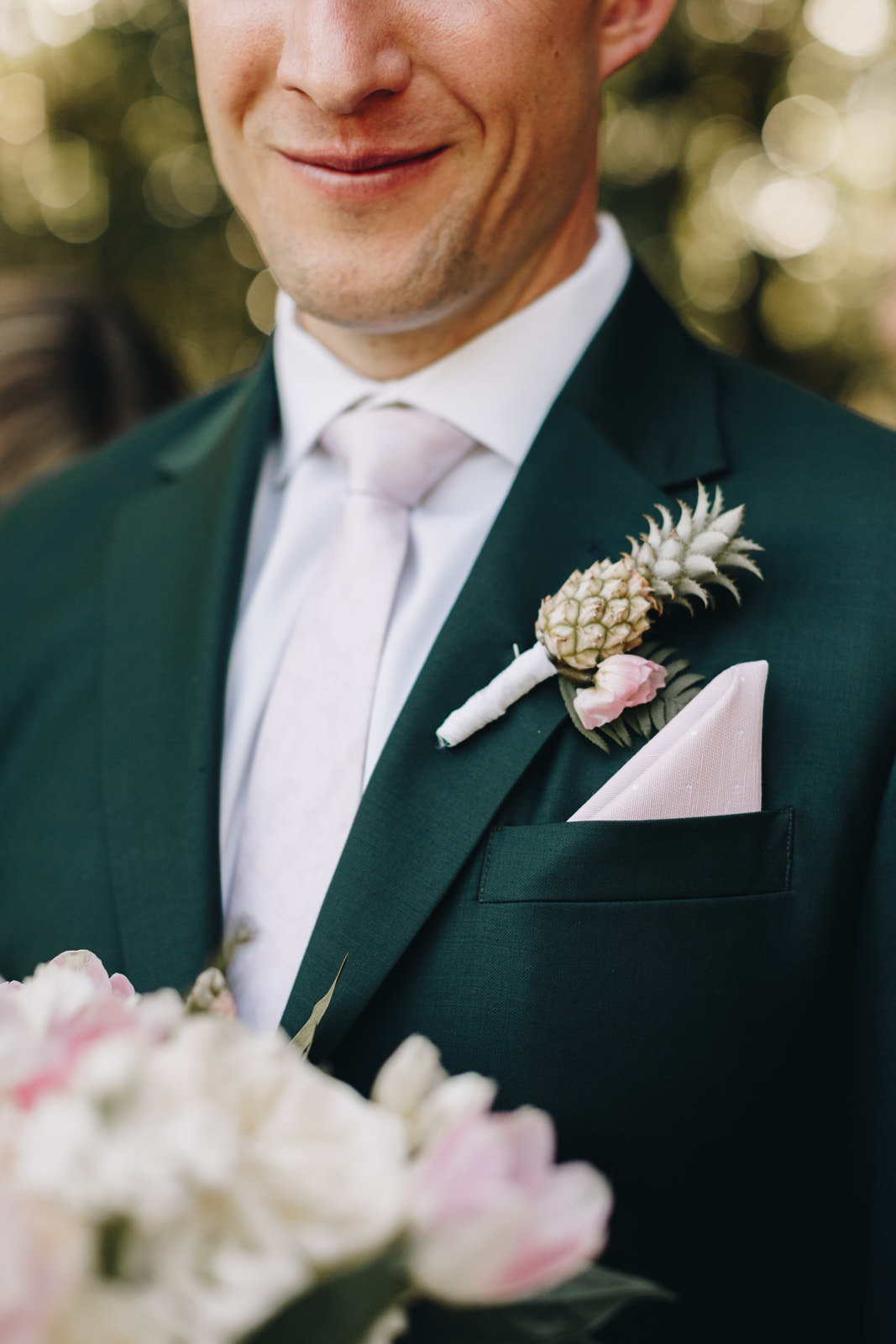 Groom with a blush tie and a pineapple boutonniere.