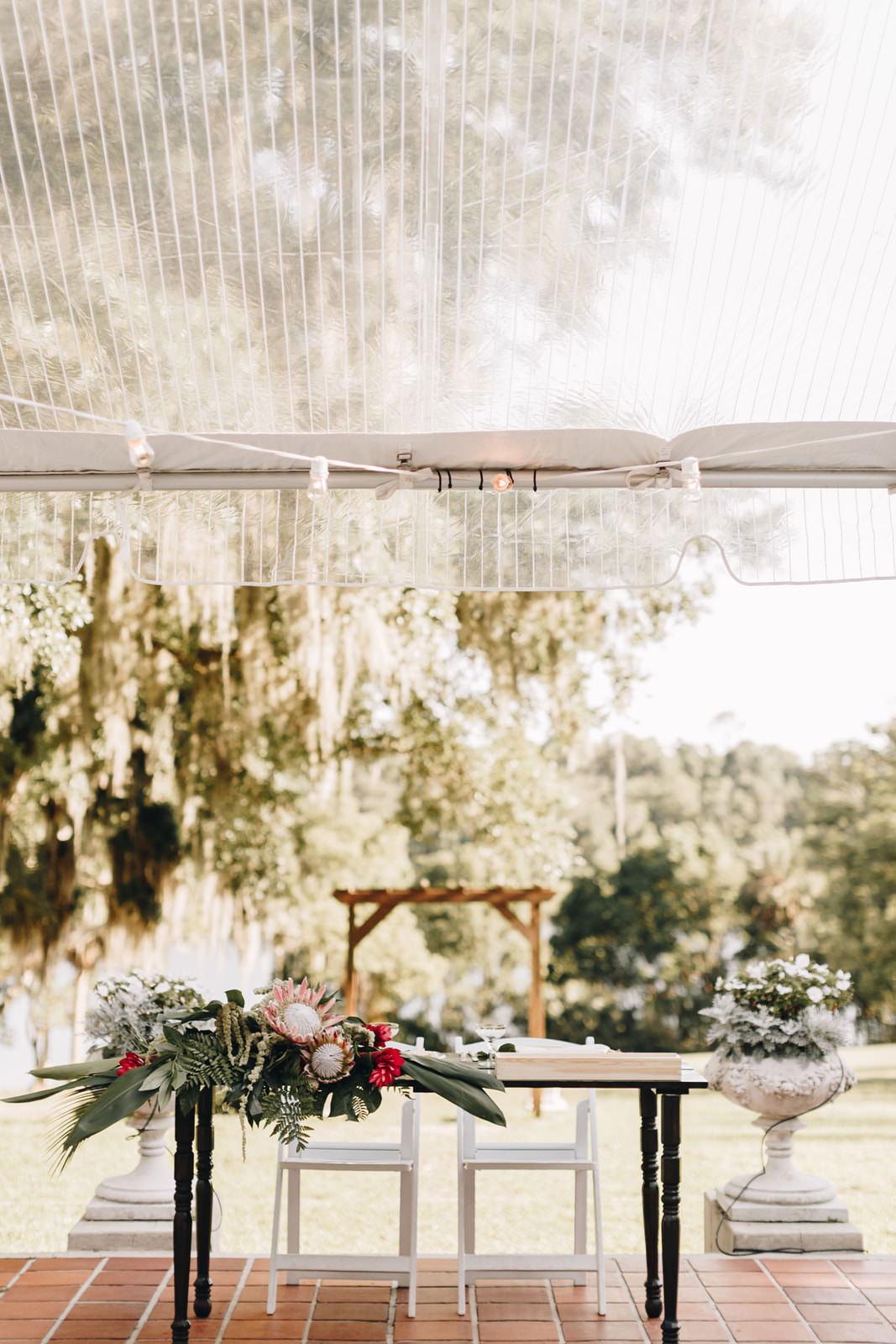 Sweetheart table with a large arrangement of greenery and flowers on the right side of the table.