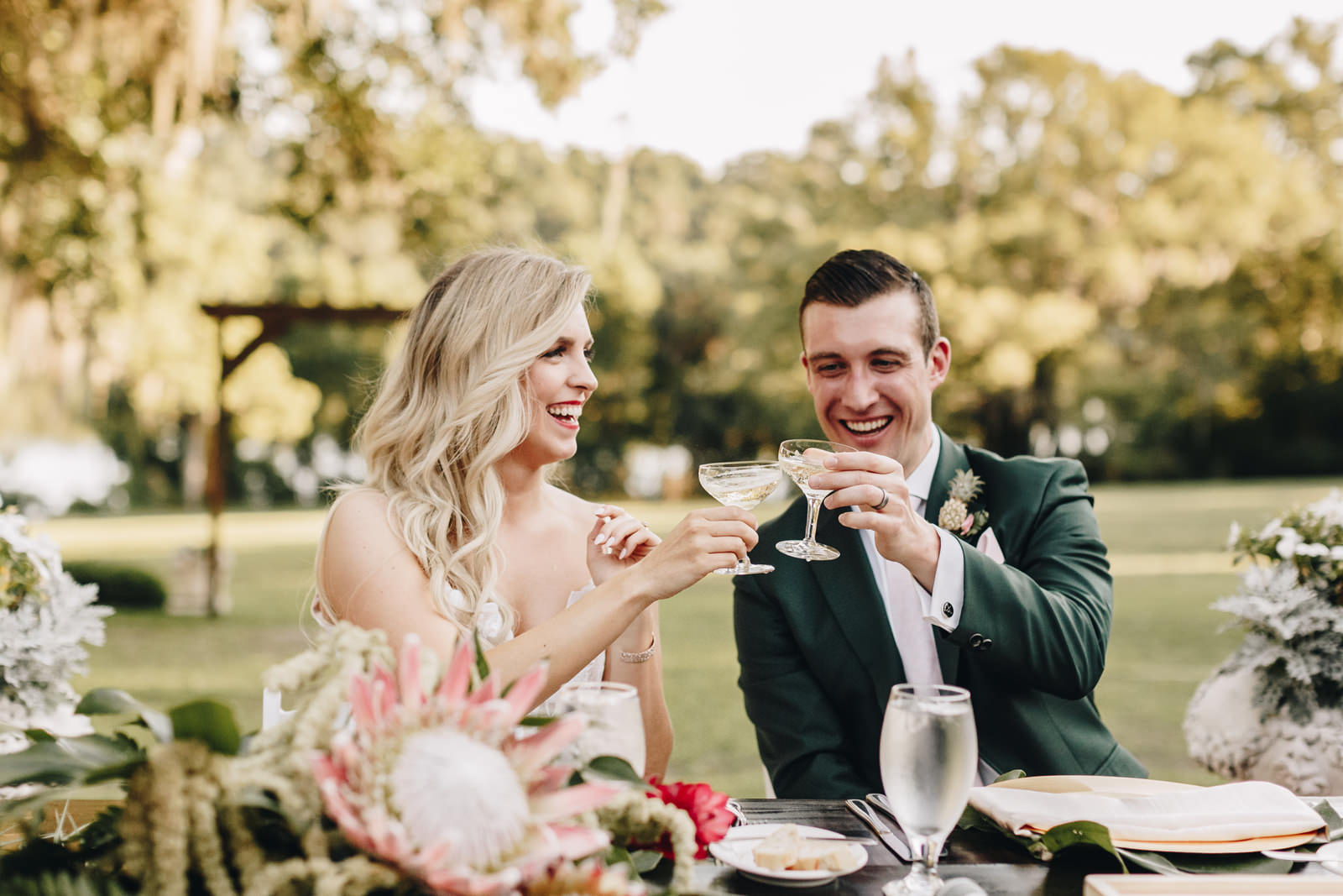 Bride and groom toasting each other at their sweetheart table.