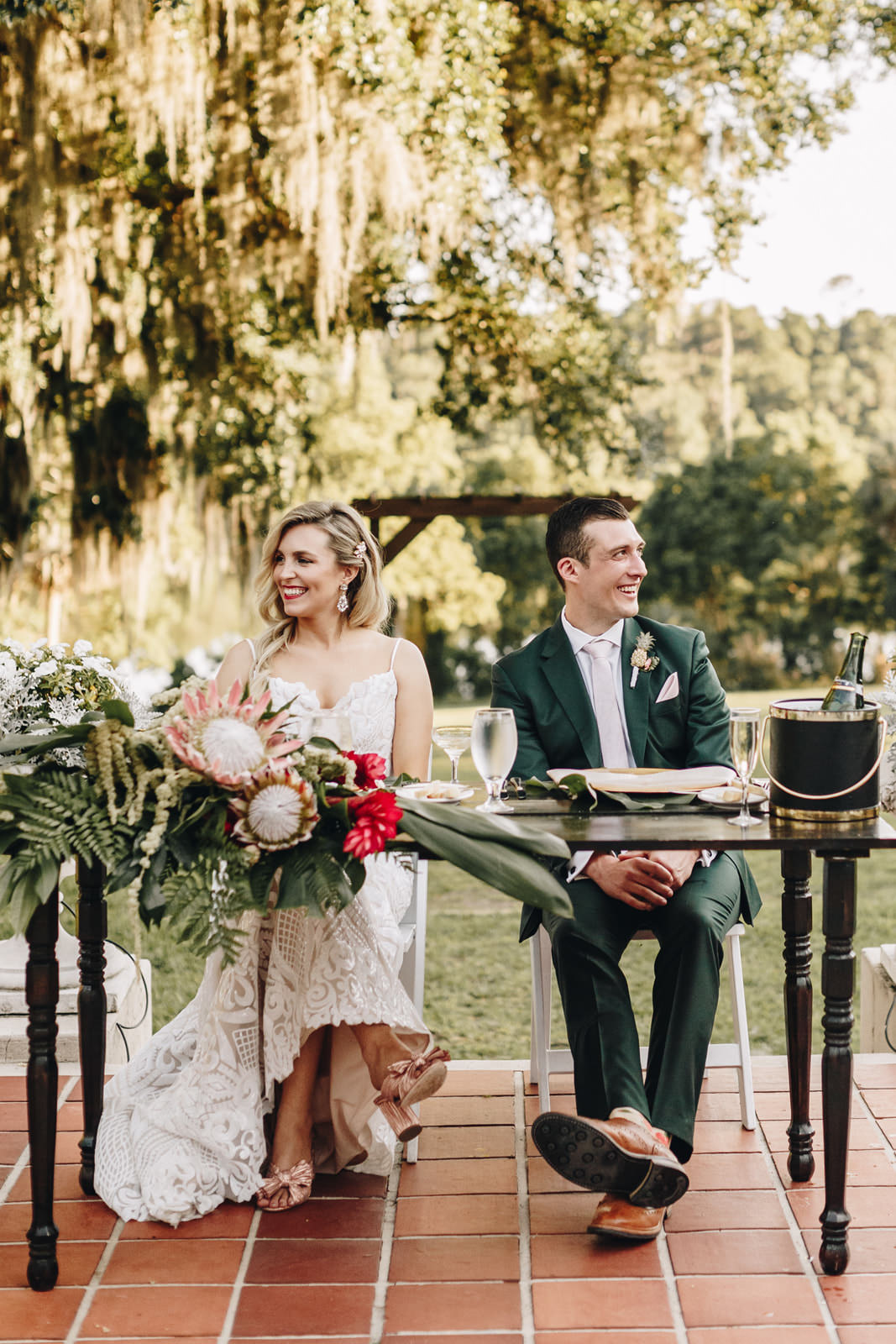 Bride and groom sitting at the sweetheart table looking at their guests.