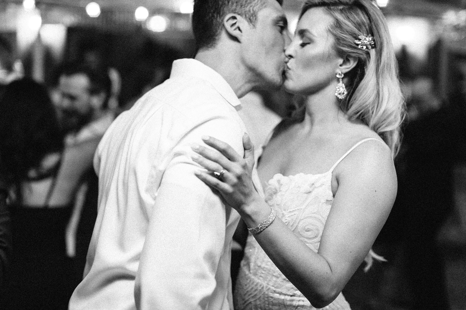 Black and white picture of bride and groom kissing.