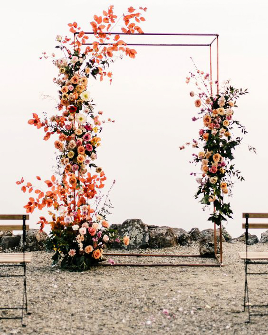 Geometric rectangle wedding ceremony arch with uneven flower arrangements on each side