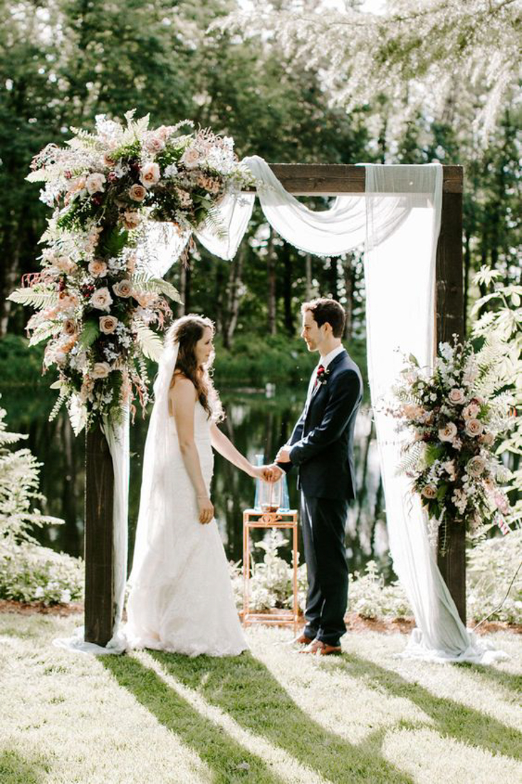 Wooden ceremony arch with tulle and flower arrangements