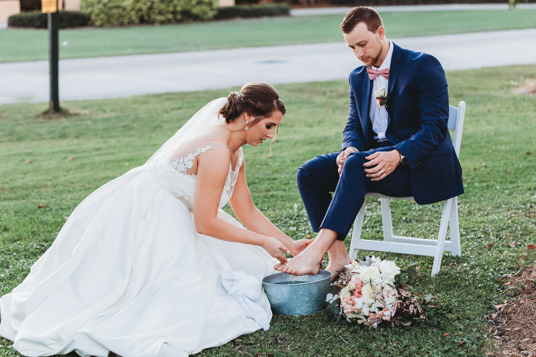 Bride and groom performing a foot washing ceremony