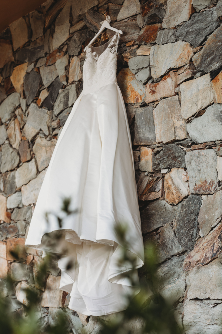 Picture of bride's dress hanging on a stone wall.
