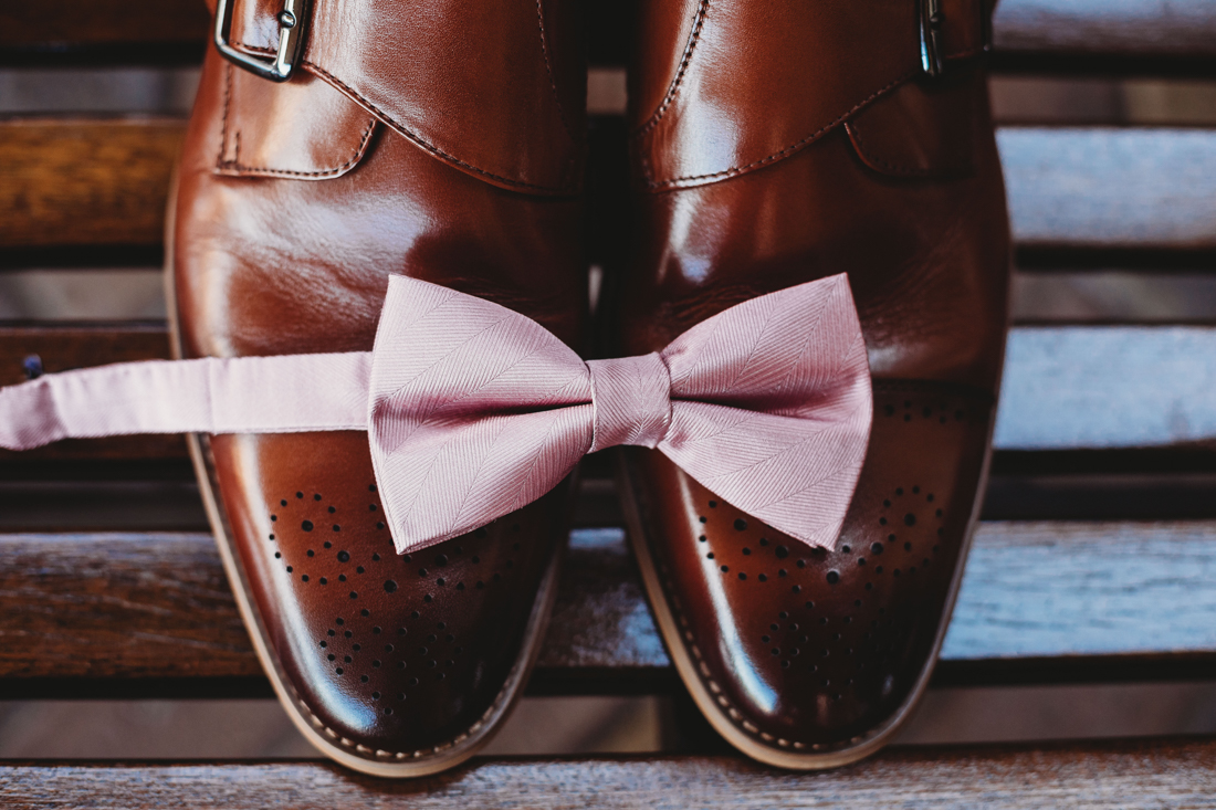 Groom's shoes with a pink bow tie over them.