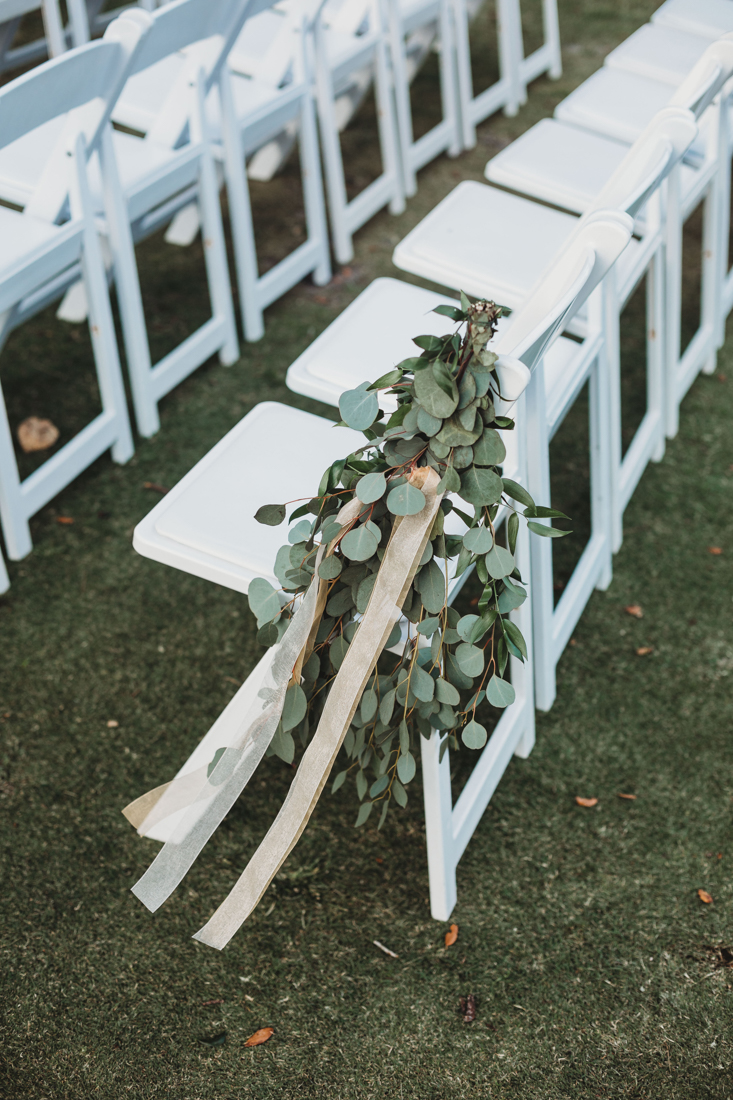 Eucalyptus bunch hanging from a chair at a ceremony.