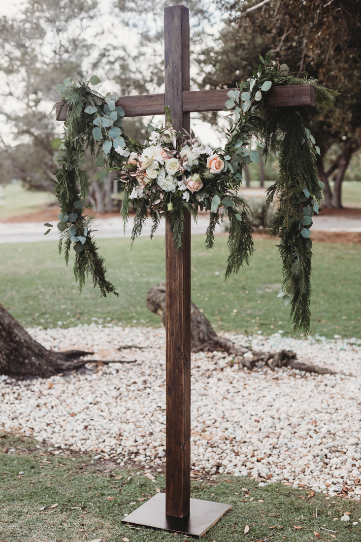 Cross ceremony arch with a eucalyptus garland.