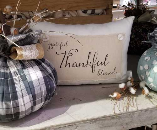 "pillow with ""grateful, thankful, blessed"" on the front at Driftwood market in Winter Garden"