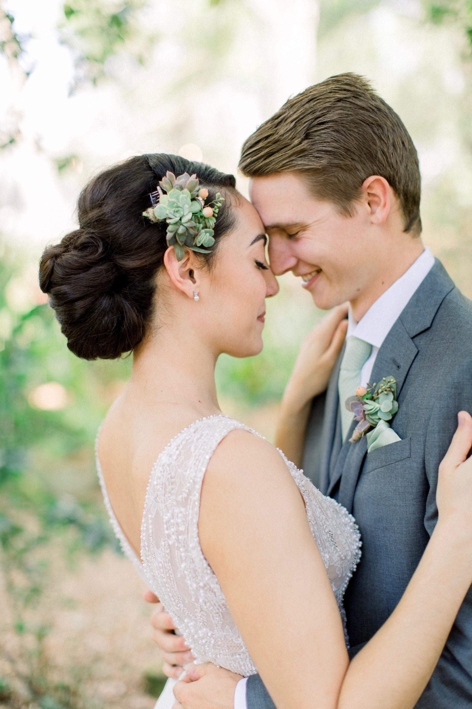 Couple touching noses, bride with an updo and succulent in her brown hair.