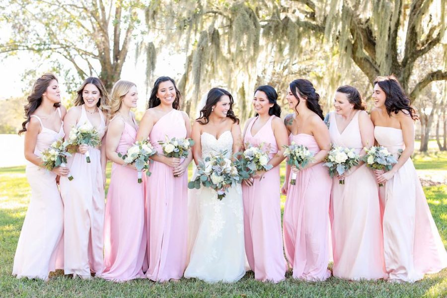 bride with her bridesmaids in pink dresses holding bouquets