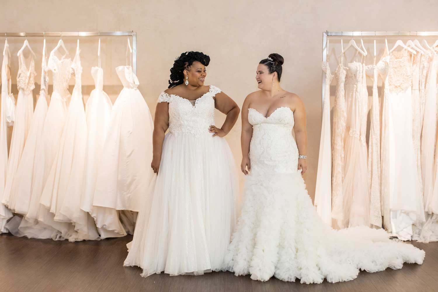 plus-size brides smiling at each other at Solutions Bridal