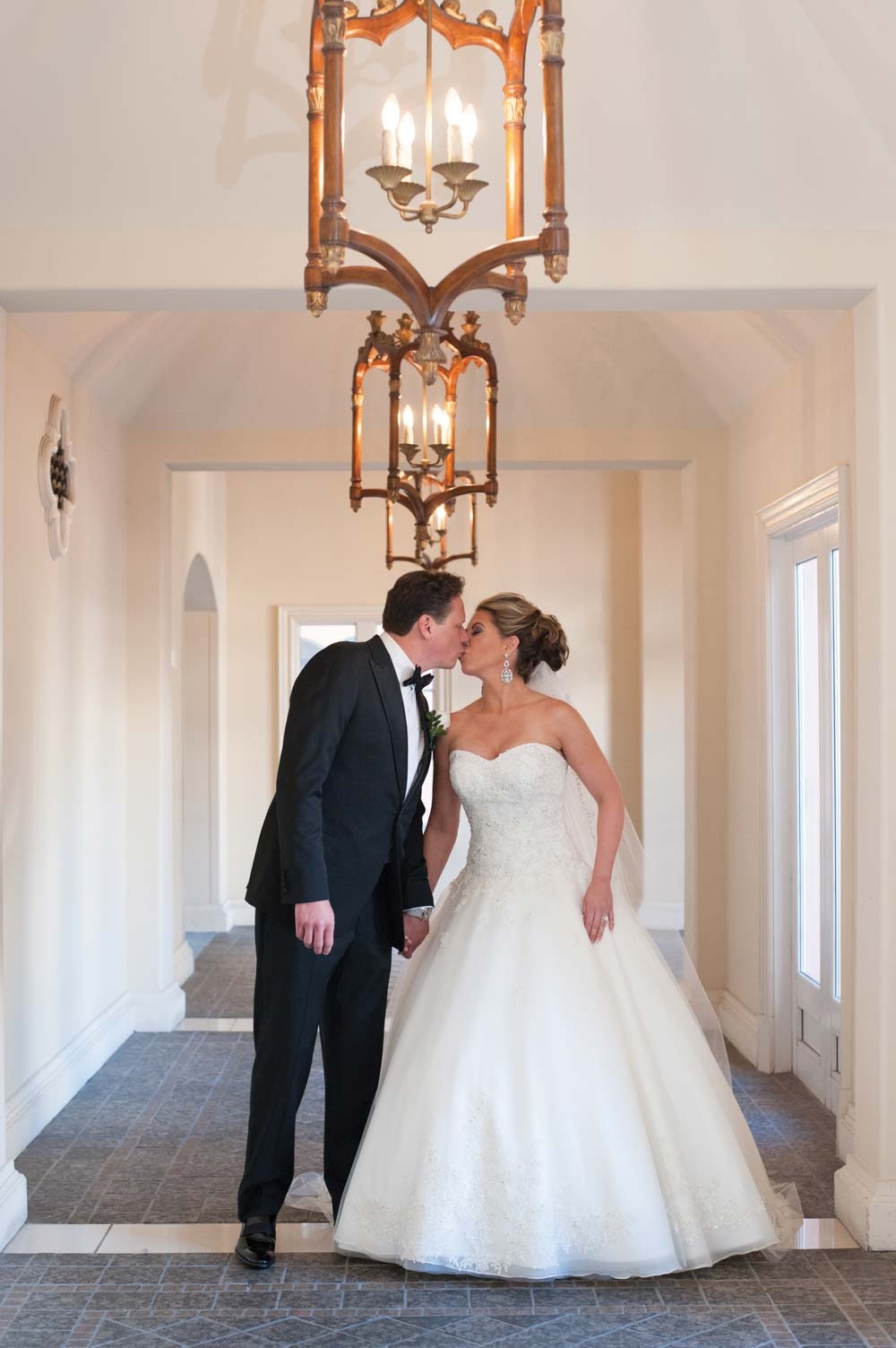 bride and groom kissing in hall way after first look