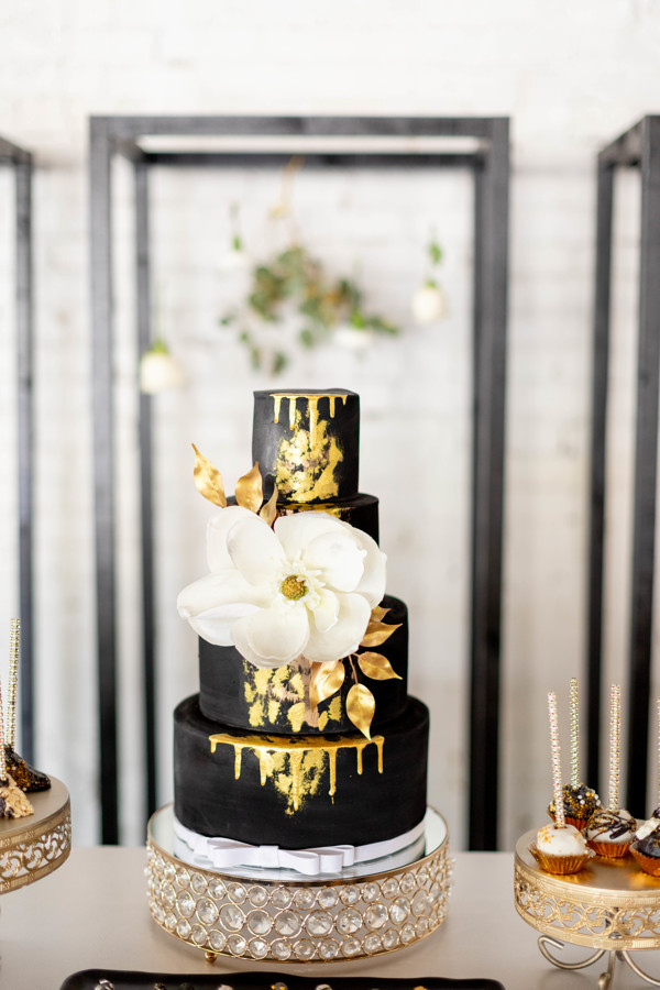 4 Tiered black wedding cake with gold foil and a white flower on the front of it.