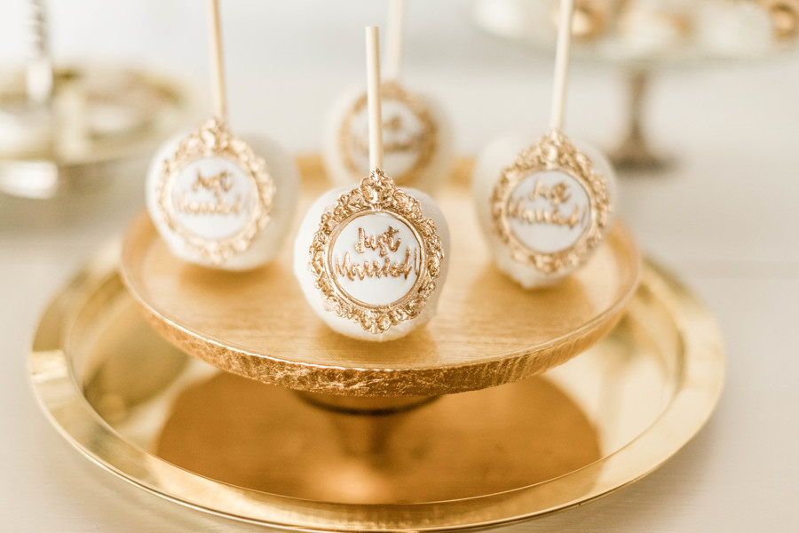 "White dipped apples with ""Just Married"" in gold, sitting on a gold cake holder."