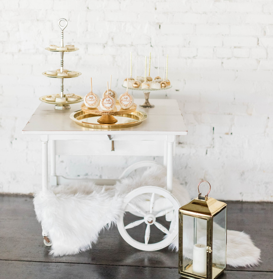 White wedding dessert table with gold holders. White dipped candied apples, white and gold cake pops, and white dipped oreos are on the table.