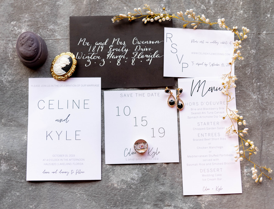 White and Black Wedding Invitation Suite flatlay with gold decorations, black earrings, and wedding rings.