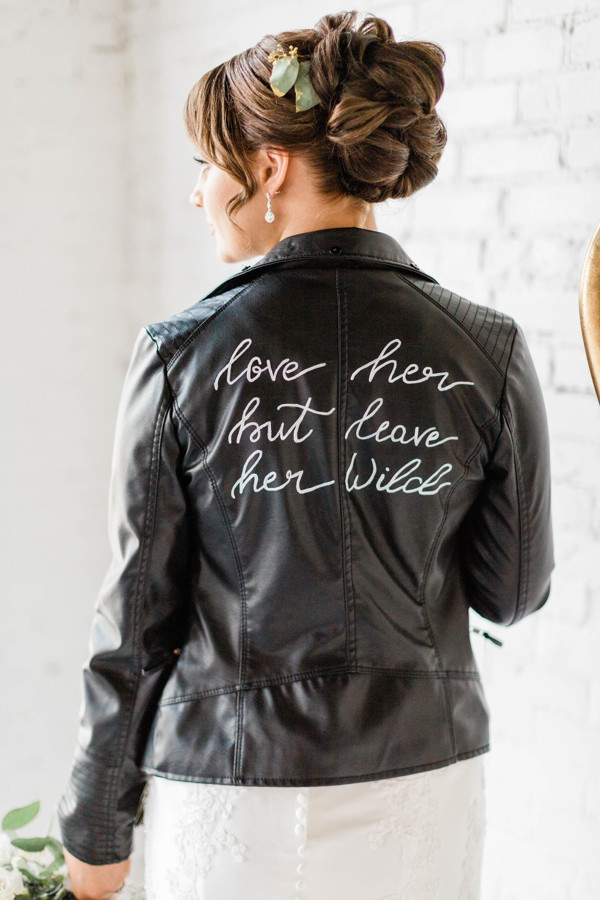 "Black bridal leather jacket with ""Love her but leave her wild"" on the back of it."
