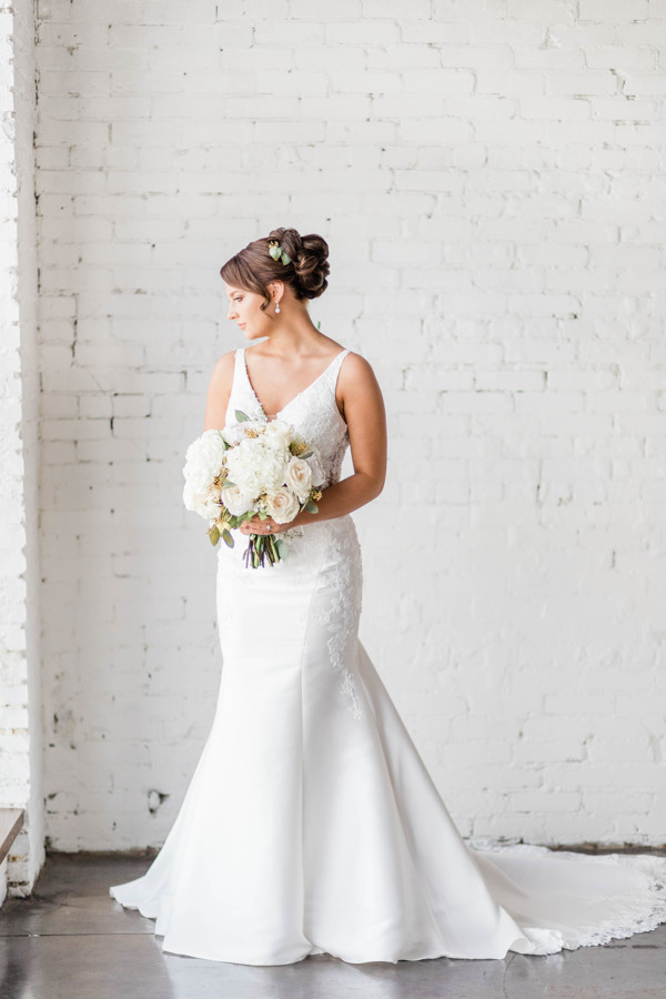 Bride standing with head to the side, holding a white wedding bouquet and her hair in a wedding updo.