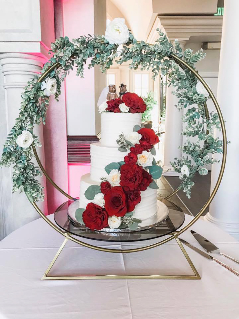 White 3 tiered wedding cake with red flowers draped down the front. Placed in a circular metal cake holder